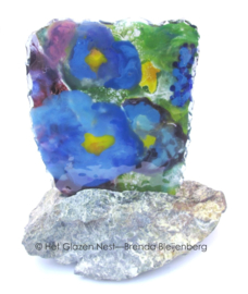 Viooltjes in glas en steen