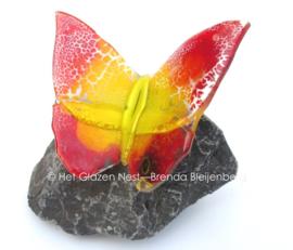 Glazen vlinder op basalt steen