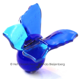 Kleine blauwe glas vlinder op blauw glas bolletje