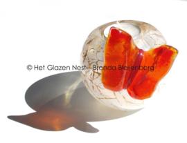 Oranje vlinder op een witte waxine-licht houder