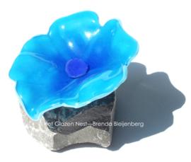 speelse abstract bloem in aqua blauw glas op steen