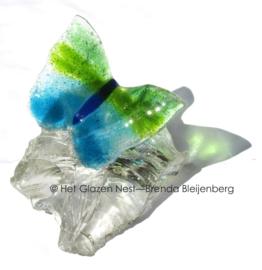 Speels groen en aqua vlinder op doorzichtig glasbrok