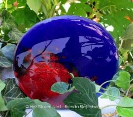 Cirkel in volle blauw en roodtinten, tegen een stuk graniet