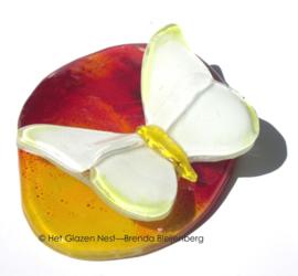 Kleine gele vlinder op oranje en rood glas