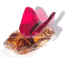 Kleine rode vlinder op ruw amberkleur glas