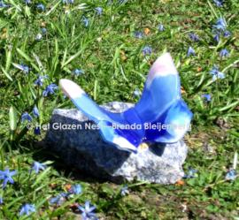 Roze en blauwe vlinder op blauwe steen