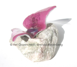 Roze vlinder  op roze en witte steen