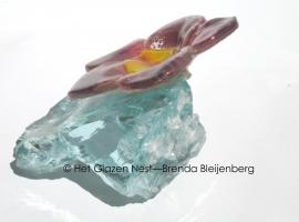 Bloem in prachtig opaal glas op een brok helder glas