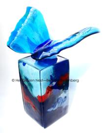 Blauwe glazen vlinder op gekleurde urn-zuil