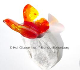 vlinder in oranje en geel op witte steen