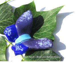 Aparte vlinder met kobaltblauw, lichtblauw, paars en witte stippen