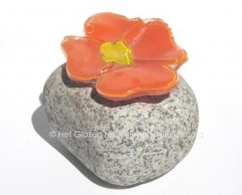 Oranje bloem in opaal glas op een Rijnkiezel