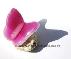 Kleine roze vlinder op steentje