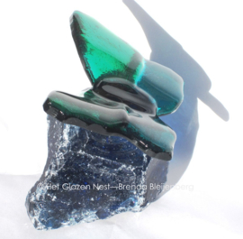 Kleine blauw groene vlinder op zeegroen glas