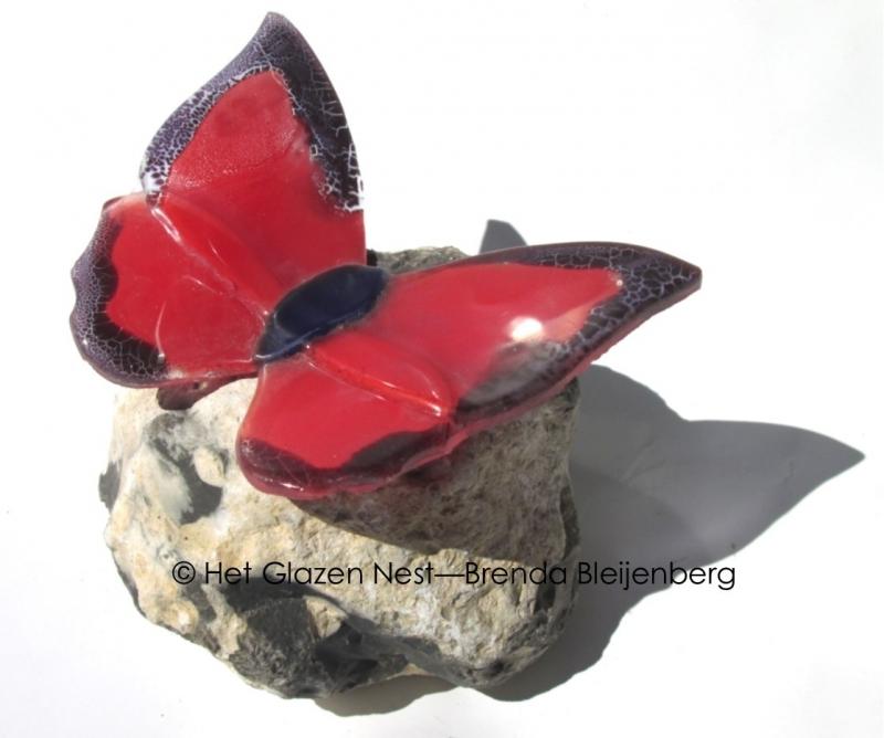 Rood met paarse vlinder op ruwe kiezel