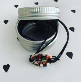 Armbandje elastiek met zwart gebloemd schelpje in blik!