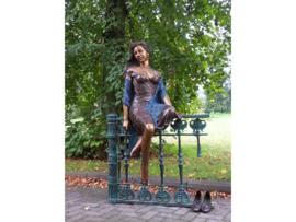 Tuinbeeld - groot bronzen beeld -  vrouw zittend op hek - Bronzartes