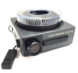 Nr.7275 -- Kodak Carousel S-AV 2000  met Kodak Vario-Retinar  zoomlens 70 - 120mm , afstandbediening met scherpstelling, voor-achteruit projectie , tevens bediening op de machine  zware halogeen lamp: 24V 250W heeft service beurt gehad en is in uitstekend