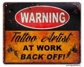 Warning Tattoo Artist at work