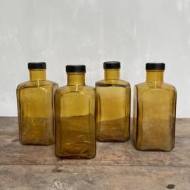 OV20110769 Set van 4 oude vierkante Franse voorraadflessen van mondgeblazen (in mal) glas in prachtig verweerde amber kleur alle 4 perfecte staat! De schroefdoppen zijn van bakeliet inhoud: 1000 ml. Afmeting: 21 cm. hoog / 9,5  cm. breed