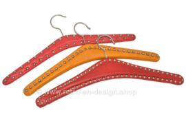 Juego de tres perchas de vinilo vintage en rojo y naranja con clavos abovedados de metal