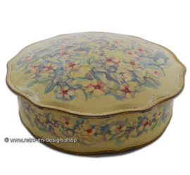 Round brocante biscuit tin with scalloped edge and pastel colored flower decor