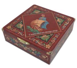 Vierkante rode blikken trommel met zeilschip en versieringen in relief