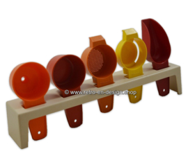 Vintage Tupperware rack with various kitchen tools
