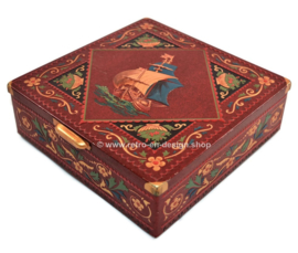 Square red tin drum with embossed sailing ship, handle and feet