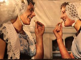 Zeeland | Fotokaart - Ansichtkaart twee vrouwen eten een Zeeuws koekje klederdracht (streekdracht) - 1960
