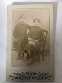Foto | Twee jongens in een jurkje op een stoel - Portrait Souvenir