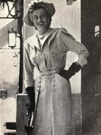 1954 | Zilvergrijze japon met knopen garnering en een 'aardige schort (met geborduurde randen' en gehaakte babycape