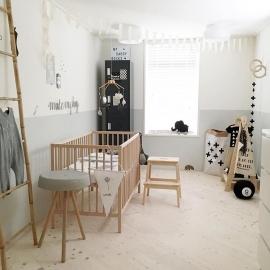 Een babykamer met wit, grijs en hout