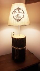 Lamp op een voet van een boomstam.