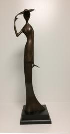 Vrouw met hoed op houten voet