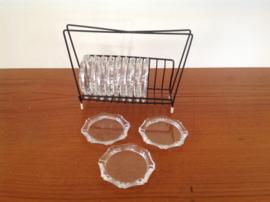 Glazen onderzetters in een rekje.