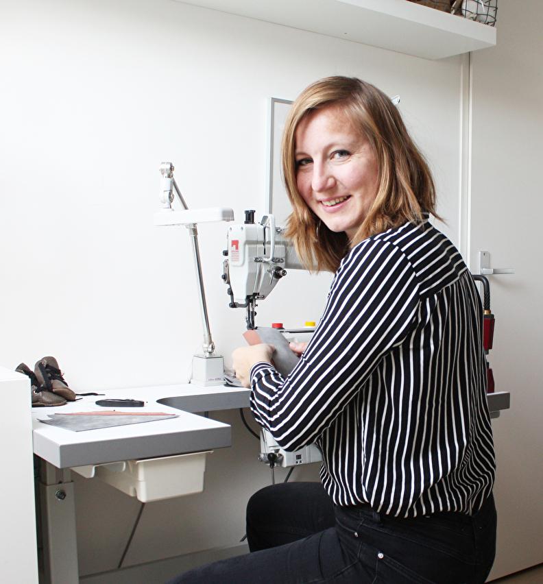 Studio LL Ellen Smit in haar atelier achter een industriele naaimachine