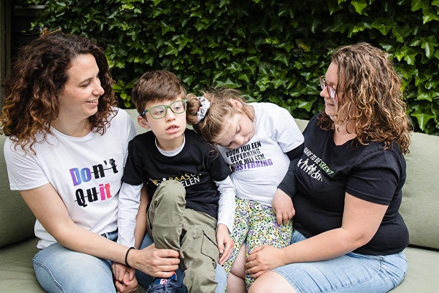 Twee vouwen, moeders met hun twee gehandicapte kinderen. ze dragen t-shirts met teksten erop.