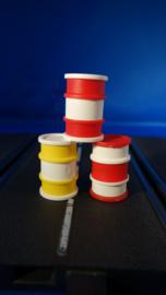 3 olievaten in 2x rood en 1x geel voor bij de racebaan