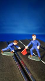 2 blauwe monteurs, 1 knielend en 1 staand met gevarenvlag