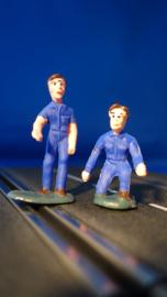 2 blauwe monteurs, 1 staand en 1 knielend