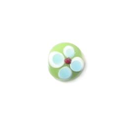 Groene platte glaskraal met witte, blauwe en rode uitsteeksels