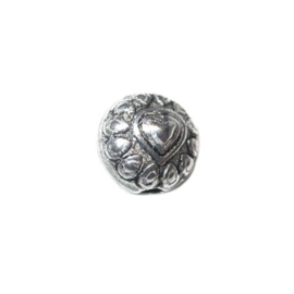 Metal bead with in the middle a heart