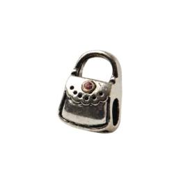 Metalen kraal in de vorm van een handtas met een klein steentje