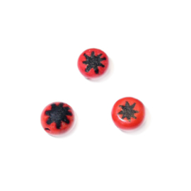 Small red glass bead with black star