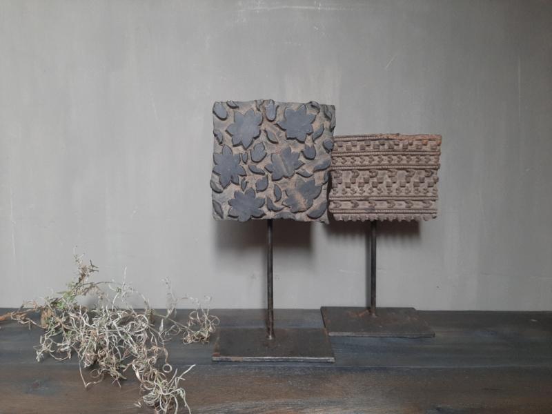 Oude batik stempel op standaard (links)