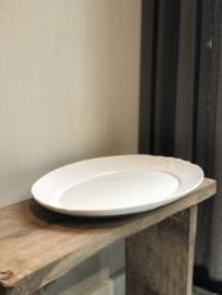 Witte serveerschaal met sierlijke details