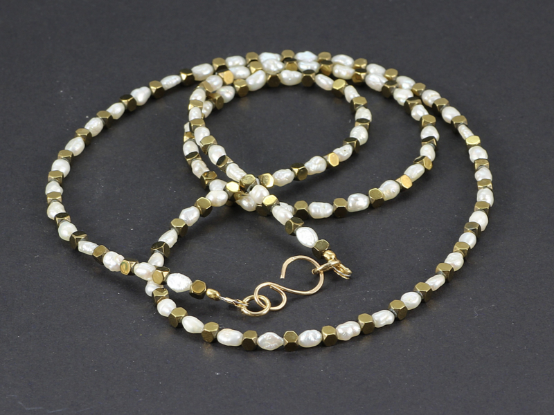 collier halflang met witte pareltjes en hematiet kubussen in goud.