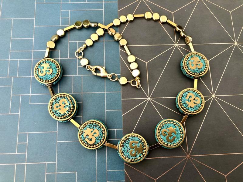 collier-hematiet goud en turkoois ohm teken