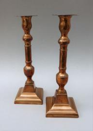 Een paar 19e eeuwse koperen kolomkandelaars op vierkante voet